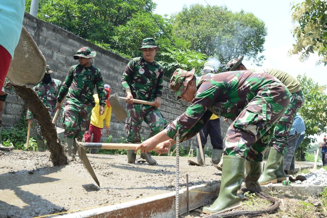 Personel Satgas TMMD 107 Mojokerto bersama warga saat mengerjakan jalan lingkungan penghubung Dusun Mojogeneng – Dusun Kupang dan Dusun Mojolebak