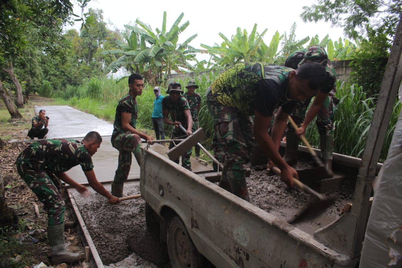 Personel Satgas TMMD menurunkan material cor yang dilansir mobil pickup dan langsung diratakan bersama warga di lokasi JUT