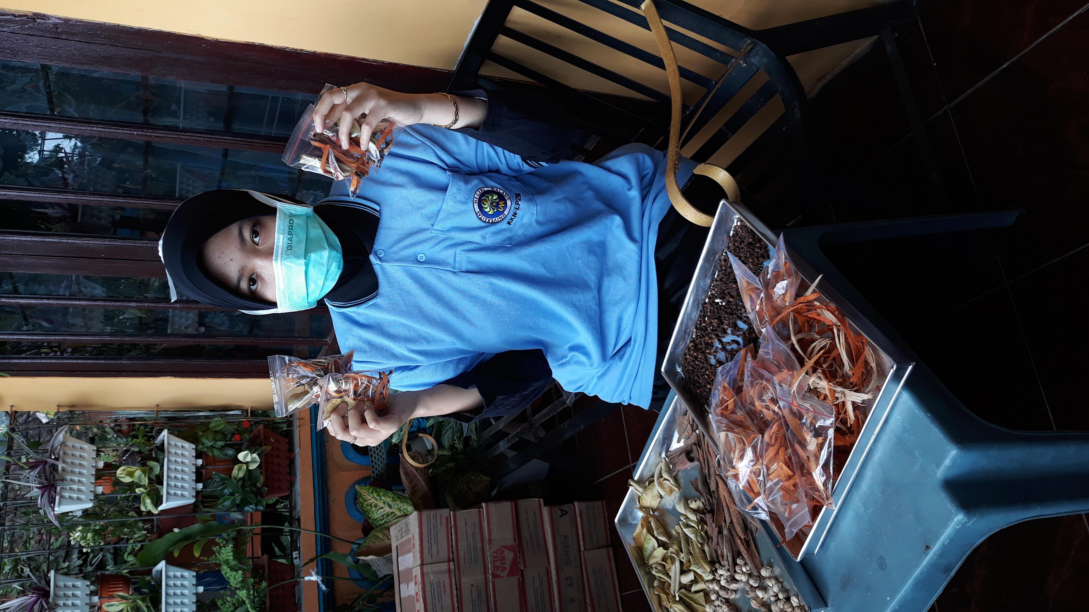Mutimmatul Lailiyah, mahasiswa KKN UM berfoto dengan wedang uwuh yang siap dibagikan ke warga Senggreng
